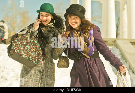 Two young women carrying bags in snow - Stock Photo