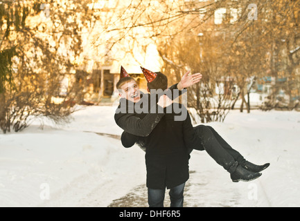 Two young male friends wearing party hats in park - Stock Photo