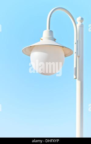 solitary white street light against the blue sky - Stock Photo