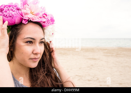 Young woman on beach with flowers in her hair - Stock Photo