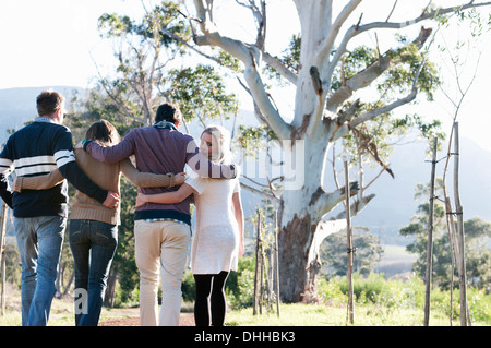 Friends walking through countryside with arms around - Stock Photo