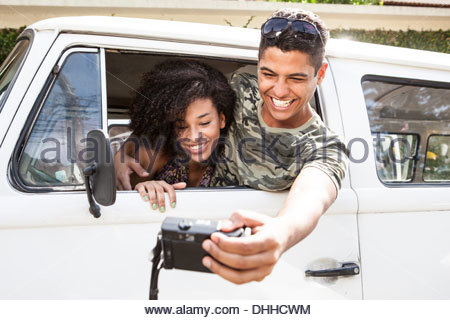 Couple taking photograph from inside van - Stock Photo