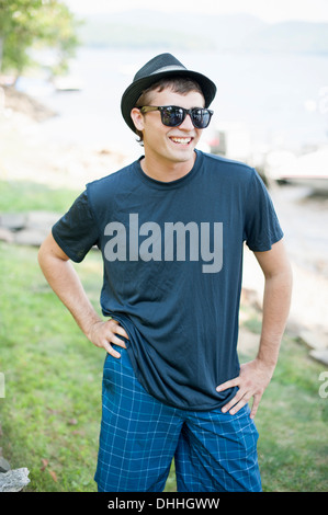 Portrait of young man wearing hat and sunglasses - Stock Photo