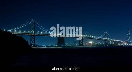 The Bay Bridge at night between Oakland and San Francisco from Treasure Island - Stock Photo