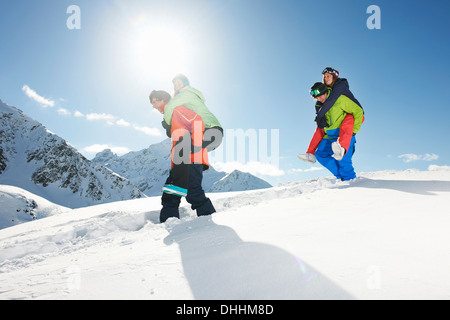 Friends giving piggy backs in snow, Kuhtai, Austria - Stock Photo