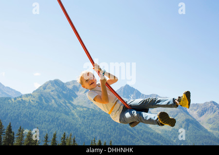 Boy playing on swing, Tyrol, Austria - Stock Photo