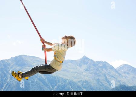 Boy having fun on swing, Tyrol, Austria - Stock Photo
