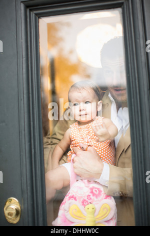 Man holding baby looking through front door - Stock Photo
