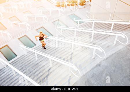 Woman running up stairs - Stockfoto