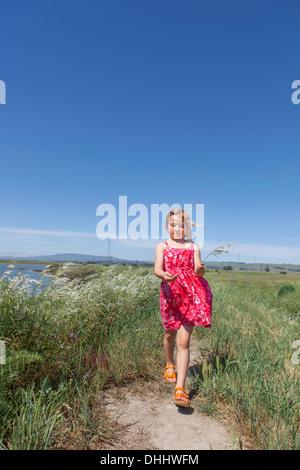 Girl walking by river marsh - Stock Photo