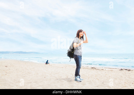 Young woman standing on beach - Stock Photo