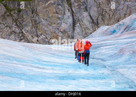 Four people walking on Mendenhall Glacier, Alaska, USA - Stock Photo