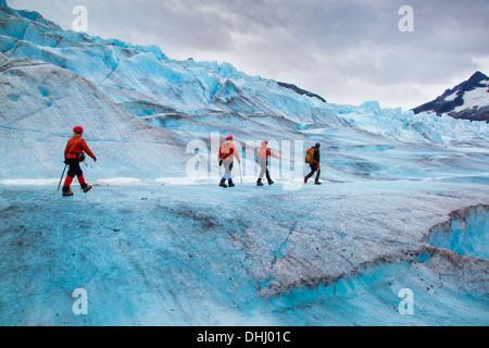Four people walking on Mendenhall Glacier, Alaska, USA - Stockfoto
