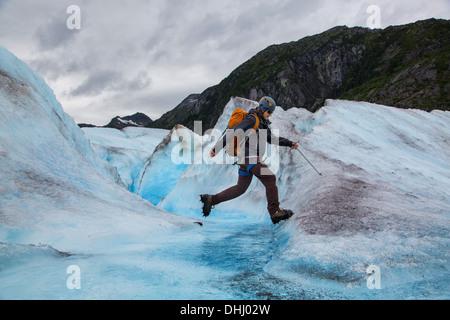 Young man walking on Mendenhall Glacier, Alaska, USA - Stock Photo