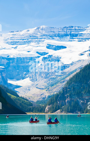 Tourists in Red canoes for hire on Lake Louise Banff national Park Alberta Canadian Rockies Canada - Stockfoto