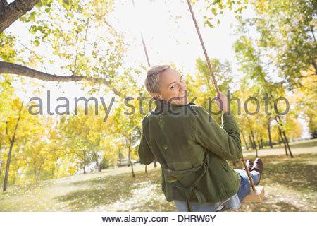 Rear view portrait of happy woman swinging - Stock Photo