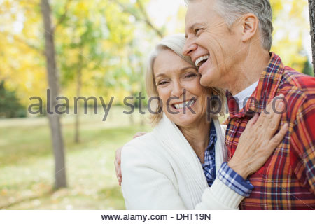 Portrait of happy mature woman with man at park during autumn - Stock Photo