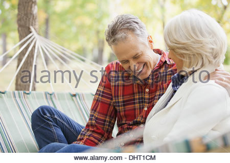 Happy mature couple sitting in hammock at park during autumn - Stock Photo