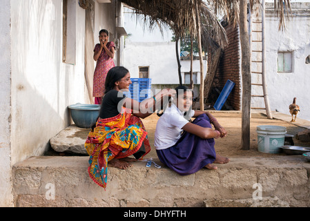 Indian mother plaiting her daughters hair for school in a rural Indian village. Andhra Pradesh, India - Stock Photo