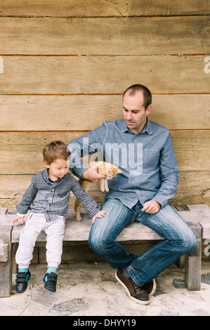 Father and son sitting on wooden bench. Father holding small cat. - Stock Photo