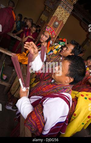 Bhutan, Thimpu Dzong, annual Tsechu, men holding ceremonial incense sticks - Stockfoto