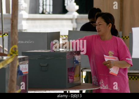 woman voting - casting her ballot by putting ballot paper ...