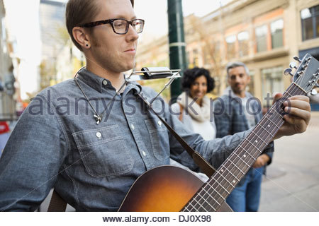Street musician entertaining pedestrians - Stock Photo