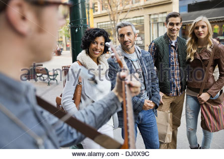 Pedestrians listening to street musician - Stock Photo