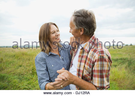 Affectionate senior couple dancing outdoors - Stock Photo