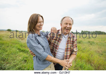 Affectionate senior couple standing in field - Stock Photo