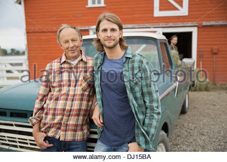 Portrait of father and son leaning on pick-up truck at farm - Stock Photo