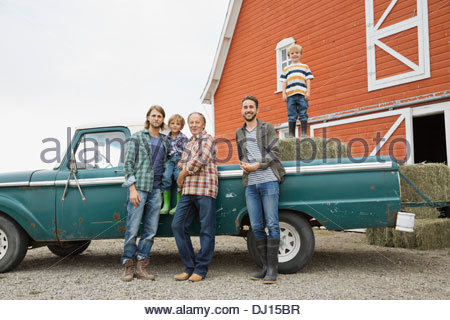 Portrait of three generation male family standing by pick-up truck - Stock Photo