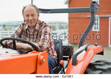 Senior male farmer sitting on tractor on farm - Stock Photo