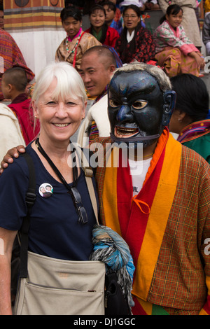 Bhutan, Thimpu Dzong, annual Tsechu senior western woman tourist with atsara clown - Stock Photo