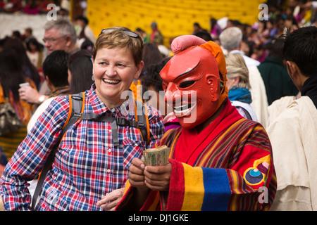 Bhutan, Thimpu Dzong, annual Tsechu female western tourist with atsara clown dancer holding money in hand - Stock Photo