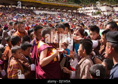 Bhutan, Thimpu Dzong, annual Tsechu crowd seeking coloured blessing threads from monk - Stockfoto