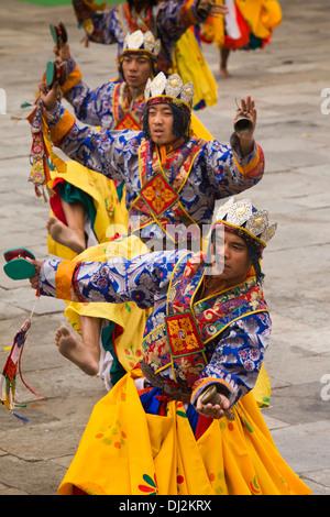 Bhutan, Thimpu Dzong, annual Tsechu, line of colourfully dressed festival dancers - Stockfoto