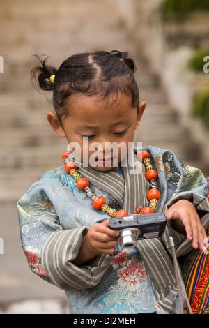 Bhutan, Thimpu Dzong, annual Tsechu, young girl in father's arms with digital camera - Stockfoto