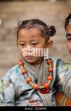 Bhutan, Thimpu Dzong, annual Tsechu, traditionally dressed young girl in father's arms - Stockfoto
