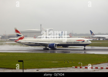 British Airways Boeing 777 jet taking off  in bad weather and rain at London Heathrow Airport - Stock Photo