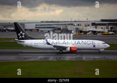 Star Alliance Boeing 737 landing at London Heathrow Airport - Stock Photo
