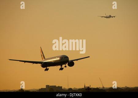 British Airways Boeing 777 landing at London Heathrow airport during sunset - Stock Photo