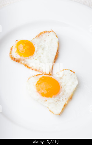 Heart shape fried eggs on the white plate - Stock Photo