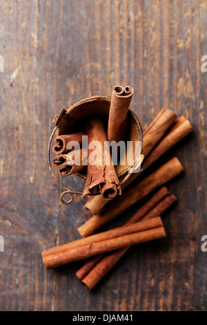 Cinnamon sticks in bucket on wooden background - Stock Photo