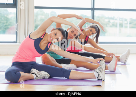 Fitness class and instructor doing stretching pilate exercises - Stockfoto