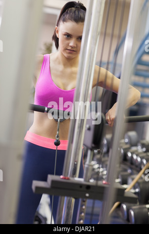 Determined woman doing exercises in gym on lat machine - Stockfoto