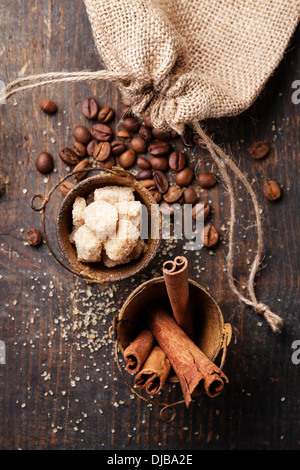 Cinnamon sticks, cane sugar and coffee beans on wooden background - Stock Photo