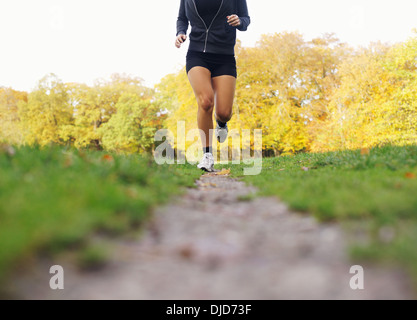 Low section image of female athlete running in park. Young woman jogging and exercising for good health. - Stock Photo