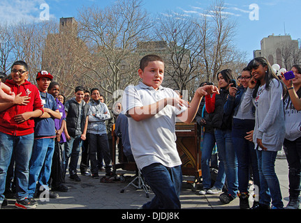 A boy on a class trip dancing in front of his friends in Washington Square Park in Greenwich Village, New York City - Stockfoto