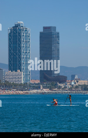Two people doing SUP or stand up paddle boarding on Barcelona beach - Stock Photo
